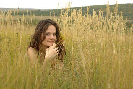 Girl with auburn hair lying in the corn field photo
