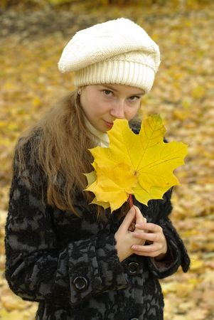 Girl holding yellow maple leaves
