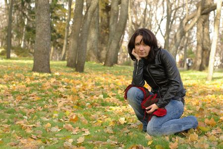 female sitting on the green grass with yellow leaves photo