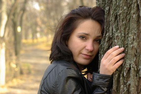 Girl touching the tree in an autumn park