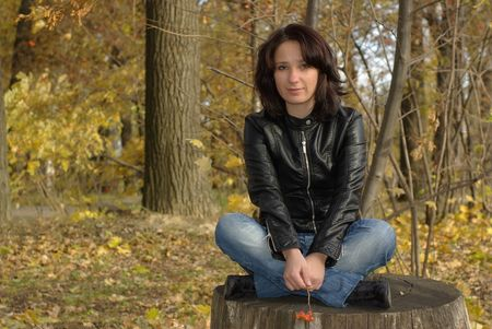 Girl sitting cross-legged on a stump in the autumn forest photo