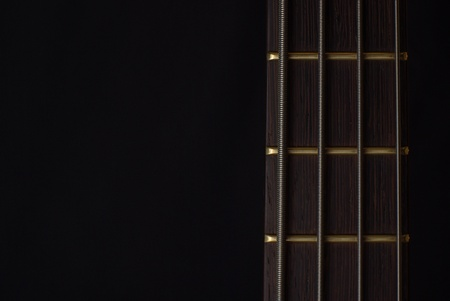 Neck of a bass guitar on black