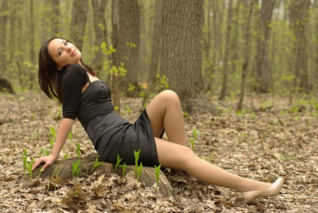Female sitting on a stump in the forest