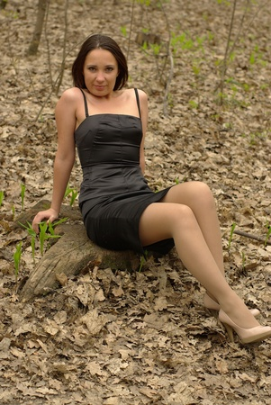 Girl sitting on a stump in the forest