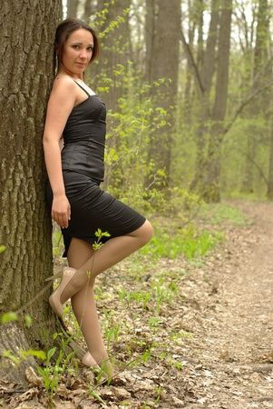 Female leaning on a tree in the spring forest