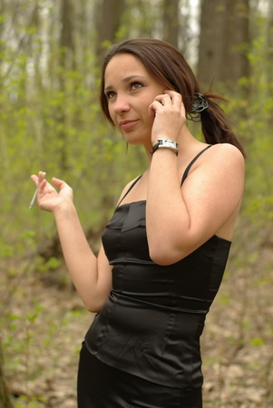 Girl talking over the cell phone smoking a cigarette photo