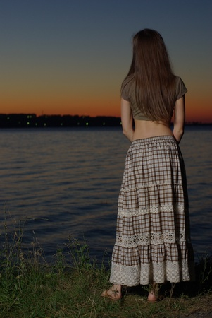 Female standing by the water in the twilight