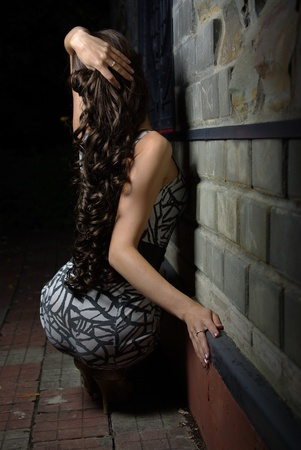 squatting: Detr�s de una mujer con cabello rizado largo