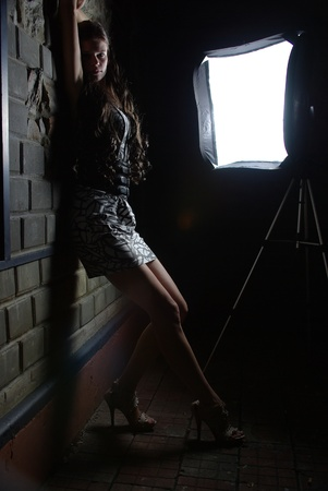 Girl leaning against a wall and a softbox photo
