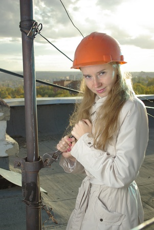 Smiling girl with a wrench in an orange helmet photo