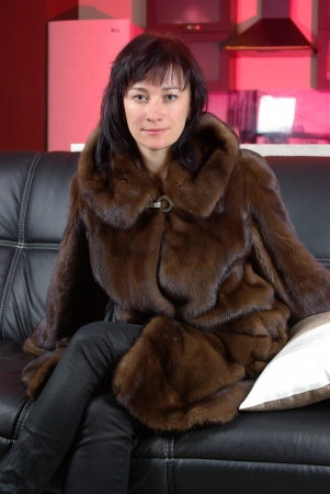 Attractive woman in a mink coat on the sofa