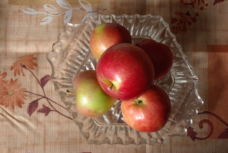 Ripe red apples in the glass bowl