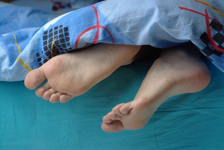 female feet: Female feet and blanket Stock Photo