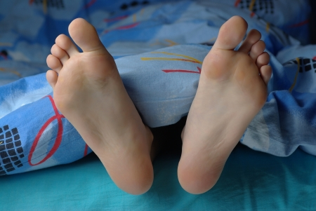 women feet: Girl feet put out from the blanket Stock Photo