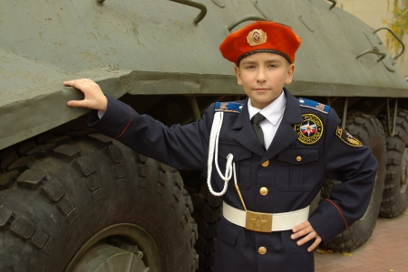 Young cadet with an armored troop carrier photo
