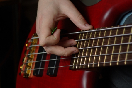 bassist: Playing on bass guitar wuth red body