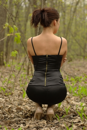 Back of pretty girl in a black dress in spring forest photo