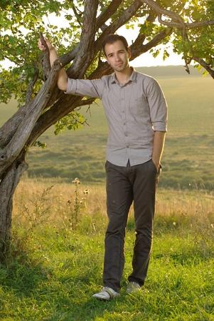 Man under tree on field photo