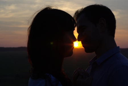Silhouette sweethearts kissing at sunset