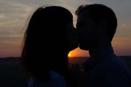 sweethearts: Silhouette sweethearts kissing at sunset