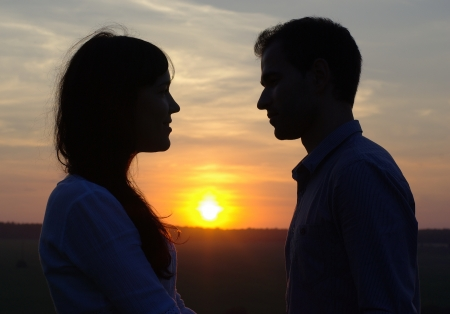 Silhouette sweethearts at sunset in a field