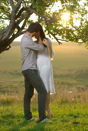 Couple kissing under tree at summer day photo