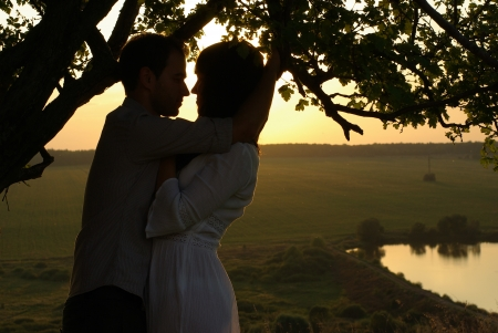 Couple kissing under tree at summer evening photo