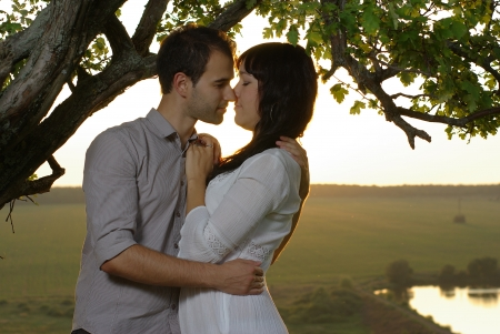 sweethearts: Couple sweethearts kissing under tree at summer day