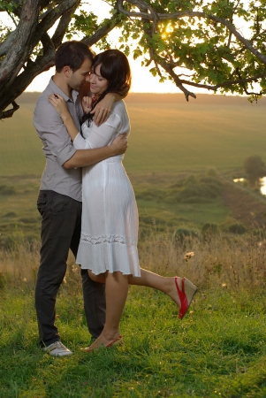 Two sweethearts kissing under tree on field photo