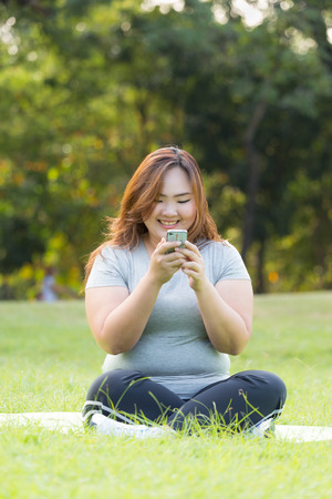 obese women: beautiful obese women playing mobile phone on the grass.