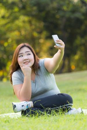 donne obese: belle donne obese seduti sull'erba e tenendo Selfie