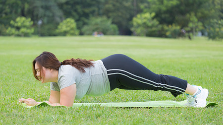 obese women planking on grass photo