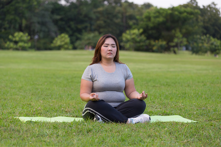 donne obese: donne obese yoga sull'erba