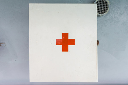 medicine cabinet: First aid box on the wall