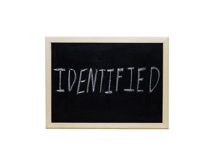 predicate: IDENTIFIED written with white chalk on blackboard.