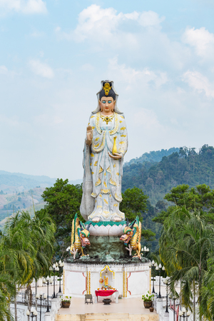 Quan Yin, the goddess of compassion and mercy, statue standing on the top of hill. Stock Photo