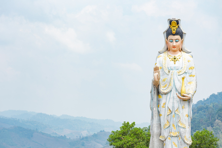 manifest: Quan Yin, the goddess of compassion and mercy, statue standing on the top of hill. Stock Photo