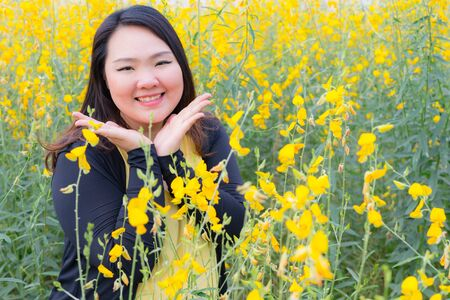 portrait of happy beautiful happy fat woman posing in sunn hemp garden. Stock Photo