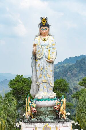 Quan Yin, the goddess of compassion and mercy, statue standing on the top of hill. Archivio Fotografico