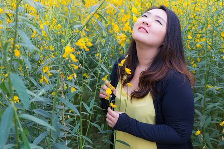 Portrait of beautiful fat woman touching and smelling sunn hemp happily in the flower garden