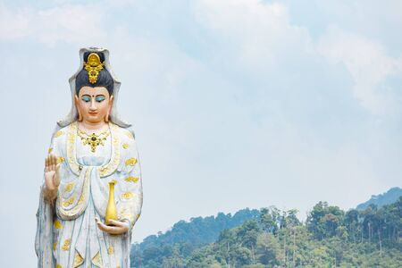 Quan Yin, the goddess of compassion and mercy, statue standing on the top of hill.
