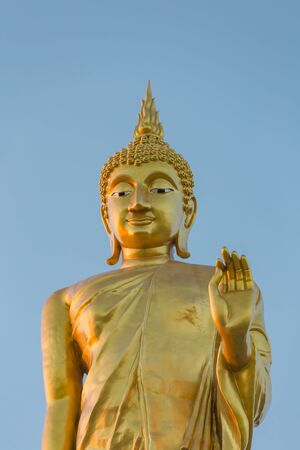 The standing buddha statue on blue sky, located in Chanthaburi, Thailand.