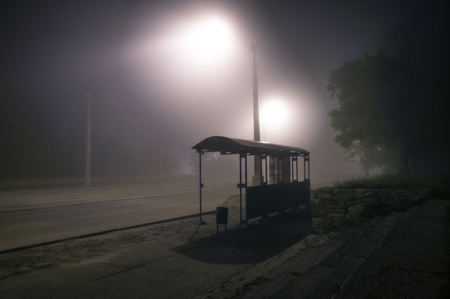Foggy street lights misty with night deserted road and trees with bus stop