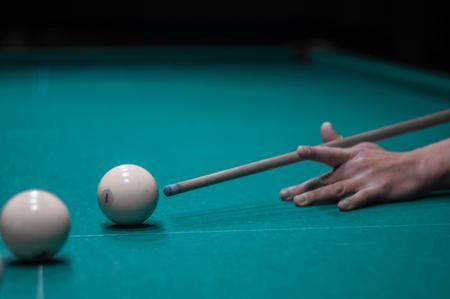 table de billard vert dans le hall avec des boules blanches avec la main de l'homme