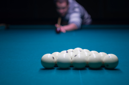 billiard green table in hall with white balls with man hand
