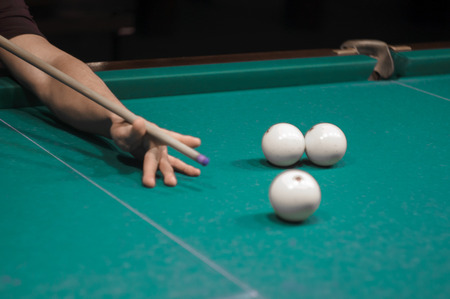 billiard: billiard green table in hall with white balls with man hand