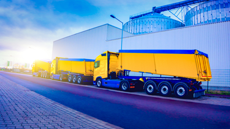 On the road for transportation of grain. the yellow truck with the trailer. Agricultural silos .Tank farm. Commercial transport. truck transport container.