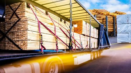 Hay una carga para el remolque del camión. Fijación de la carga en el remolque. Camión en descarga en almacén. Camión en la carretera. Transporte comercial. contenedor de transporte de camiones