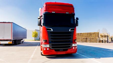 Budynek logistyki samochodów ciężarowych. czerwona ciężarówka na drodze
