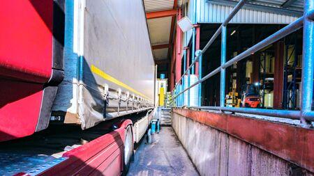 Camion de fret au bâtiment d'entrepôt. le camion avec la remorque au chargement. Remorque sur chenilles